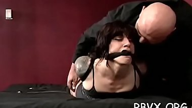 Bitch gets a ball gag in her mouth while being strapped to ottoman